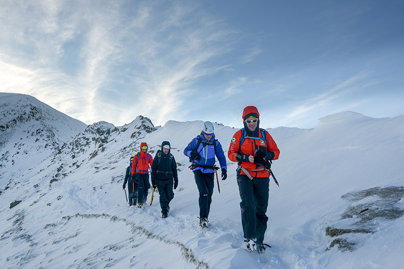 A group course on a gentle descent down a snow covered fell.
