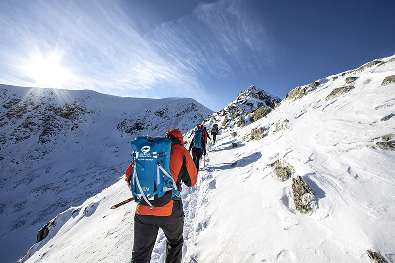Group course on a gentle ascent of a high snow-covered fell.