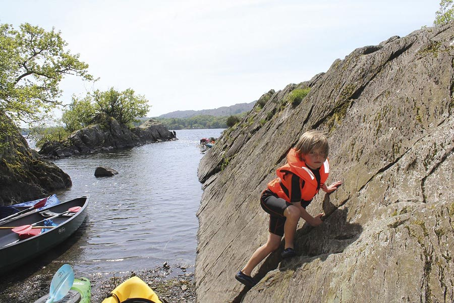 Child climbing onto a lake island from a kayak