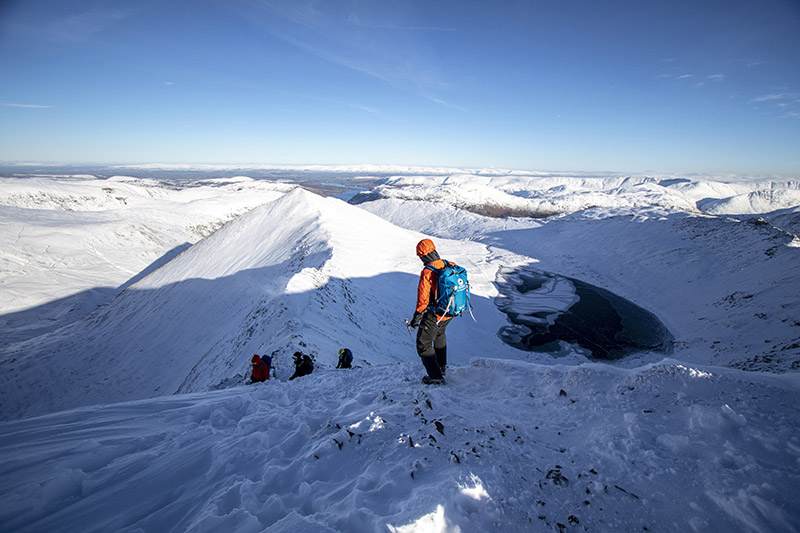 A winter skills course in the snow on Helvellyn looking down at an icy tarn