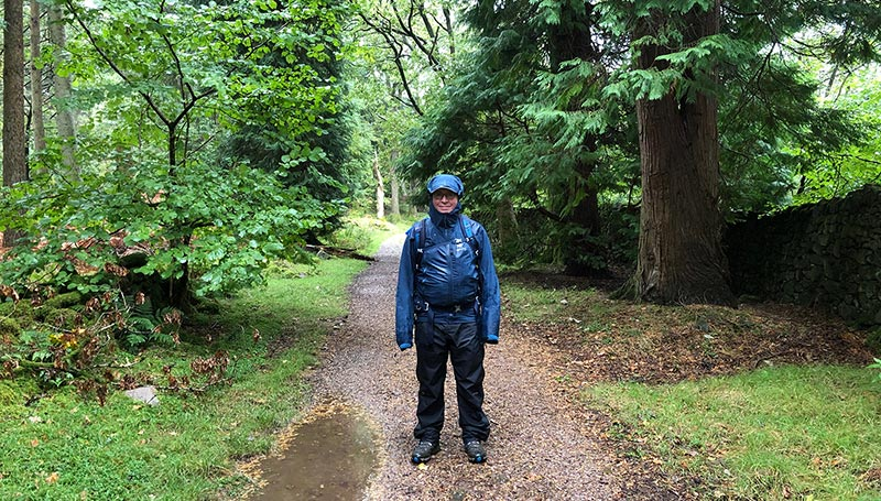 A man in full waterproofs on a woodland path in the rain