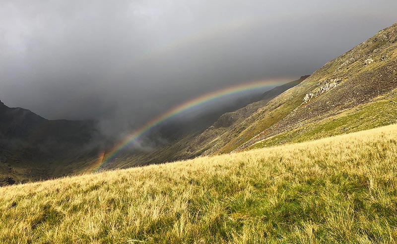 A rainbow over a Lake District valley.