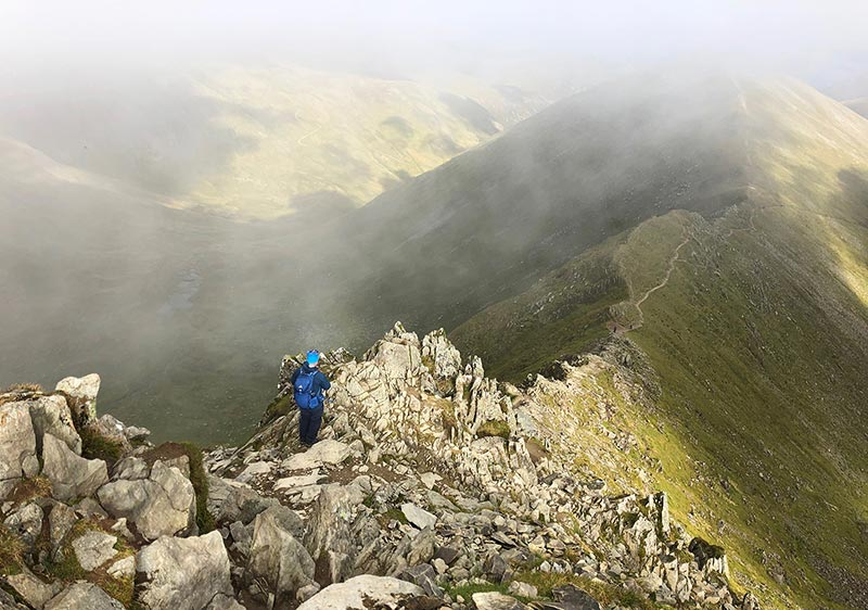 A walker on a steep, rocky mountain edge in the Lake District